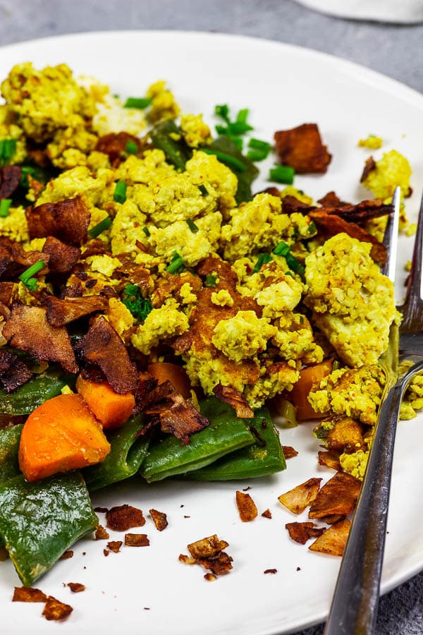 Vegan scrambled eggs with coconut bacon and veggies