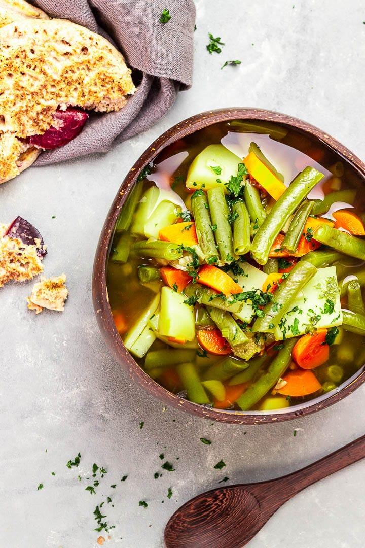 Vegane grüne Bohnensuppe mit einer kräftigen Gemüsebrühe, Kartoffeln und Karotten