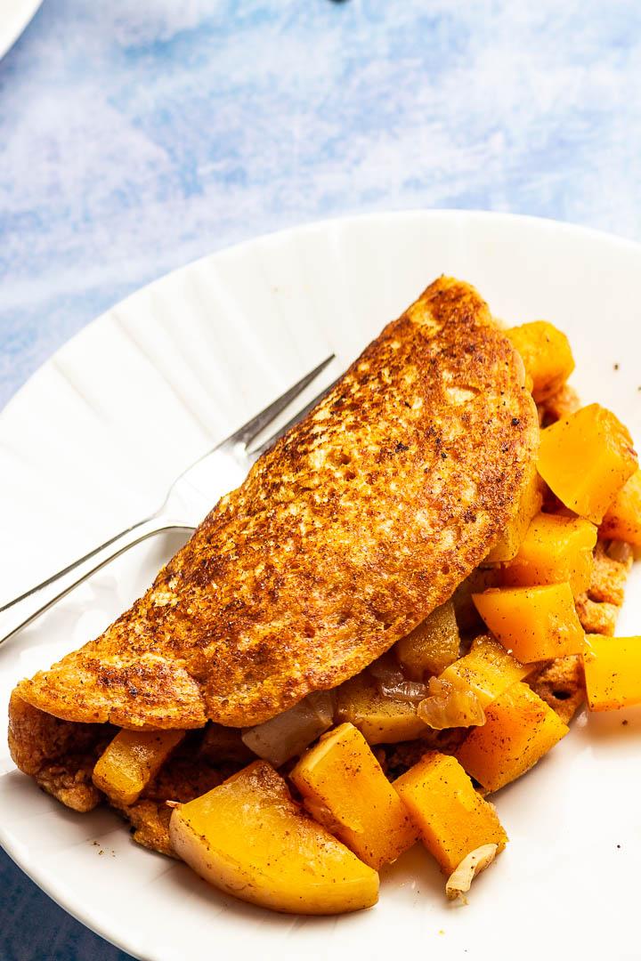 Veganer Omelette zubereitet aus Kichererbsenmehl gefüllt mit Kürbis. Ein leckeres Frühstück was du auch asl Abendessen essen kannst.
