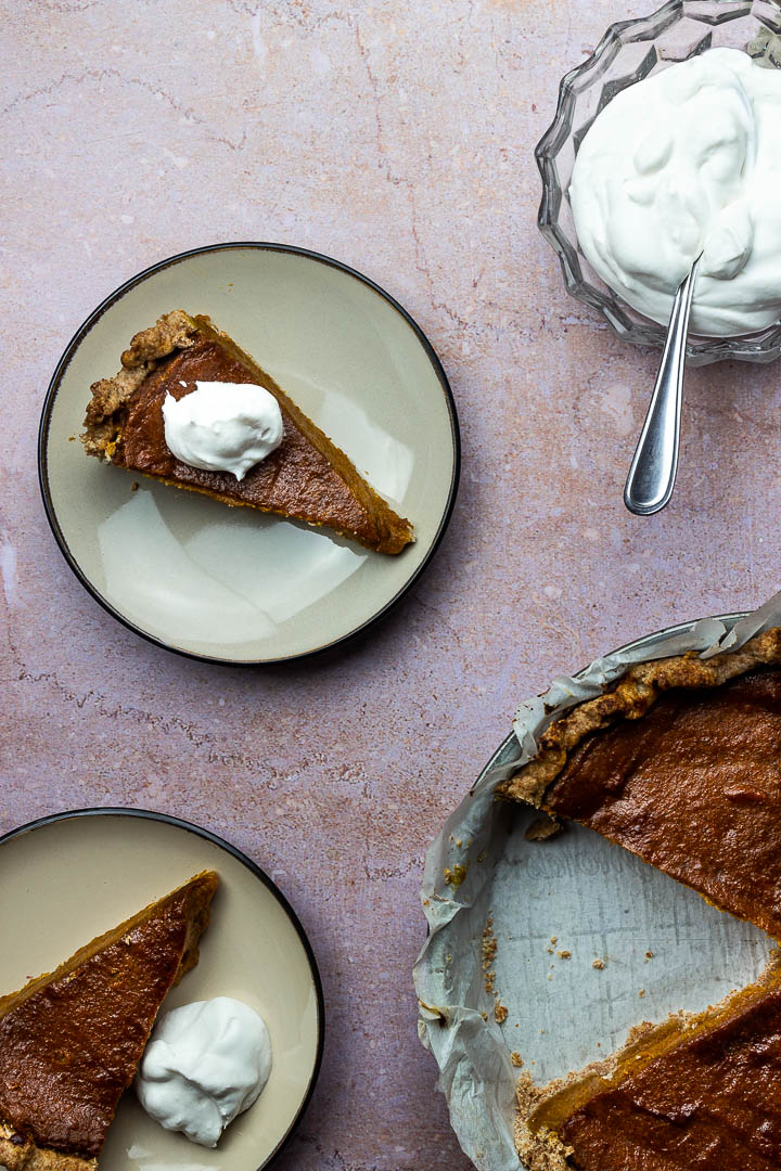 Vegan Pumpkin Pie Slice on a Plate with Whipped Coconut Cream for a Thanksgiving Dessert