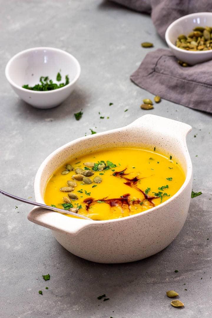 Vegane geröstete Kürbissuppe welche cremig ist und ohne Öl zubereitet. Getoppt mit Kürbiskernen, Balsamico und Kräutern