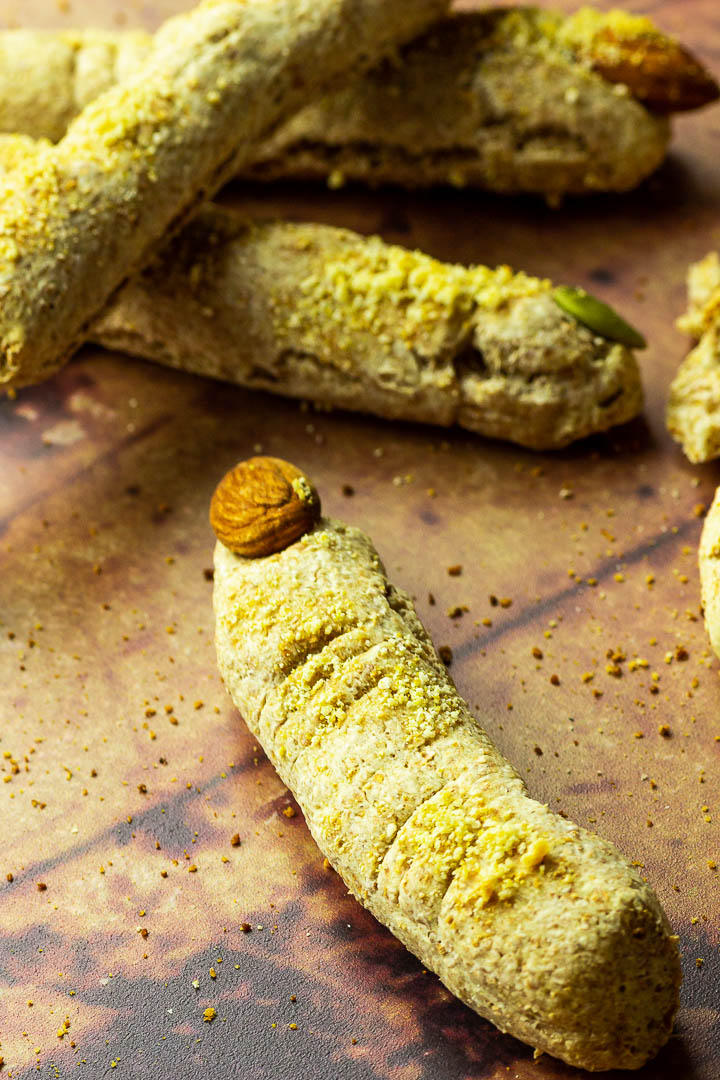 Close up of a vegan witch finger cheese bread stick made of pizza dough with vegan parmesan and almond or pumkin seed fingernails