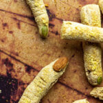 Halloween Bread Sticks in shape of witch fingers with vegan parmesan cheese and Almond / Pumpkin Seed Fingernails. Crunchy Fluffy Bread Sticks made of whole spelt / wheat pizza dough