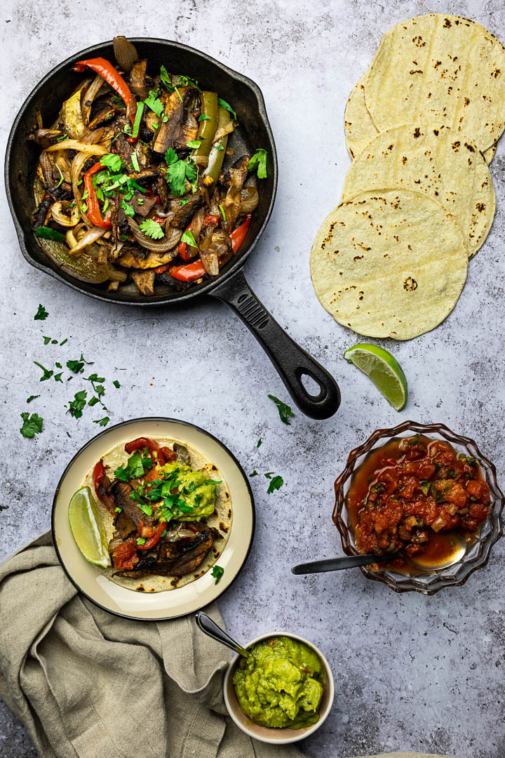 Vegan Sheet Pan Fajitas with Portobello Mushrooms, Bell Peppers, Onions served in a skillet pan with tortillas, salsa and guacamole