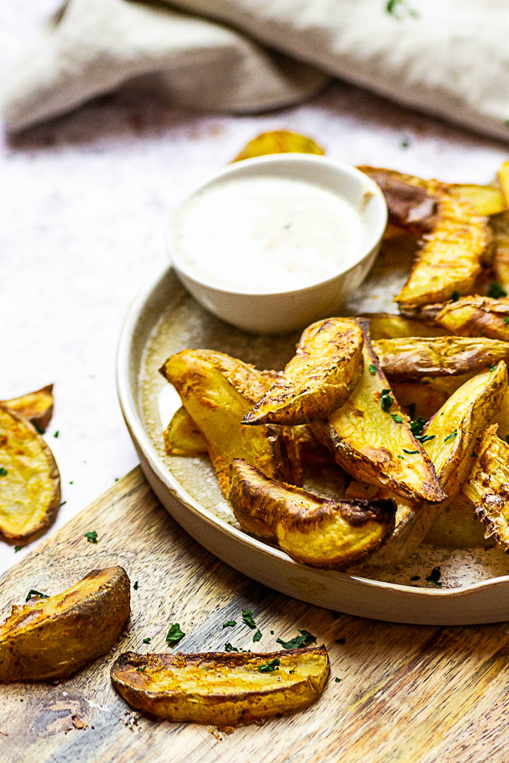 Homemade oven baked whole food plant-based potato wedges. These vegan french fries are made without oil and super quick baked.