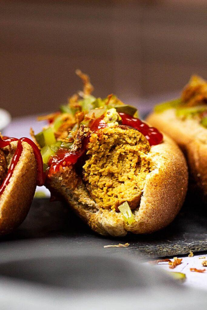 Vegane Wurst zubereitet aus Seitan (Gluten), Kichererbsen, Tahini und Rote Bete. Vegetarische Würstchen als Hot Dog serviert mit Senf, Ketchup, Gewürzgurken und Röstzwiebeln