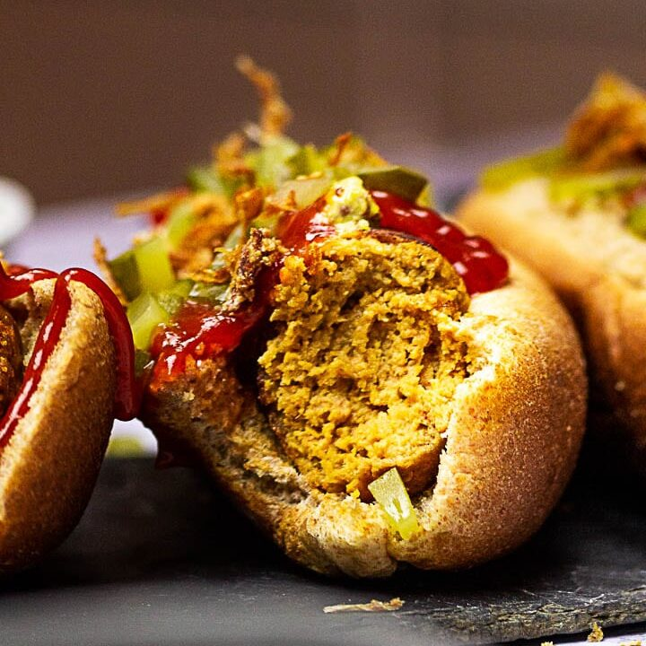 Vegan Hot Dogs made with Seitan (Gluten), Chickpeas, Tahini, Beetroot. Vegetarian Hot Dog with Mustard, Ketchup, Pickles and french fried onions