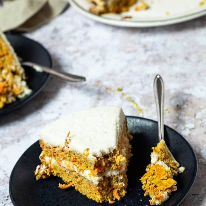 One Piece of Vegan Carrot Cake on a plate with a fork. The fork has some of the carrot cake on top. In the back the whole carrot cake.