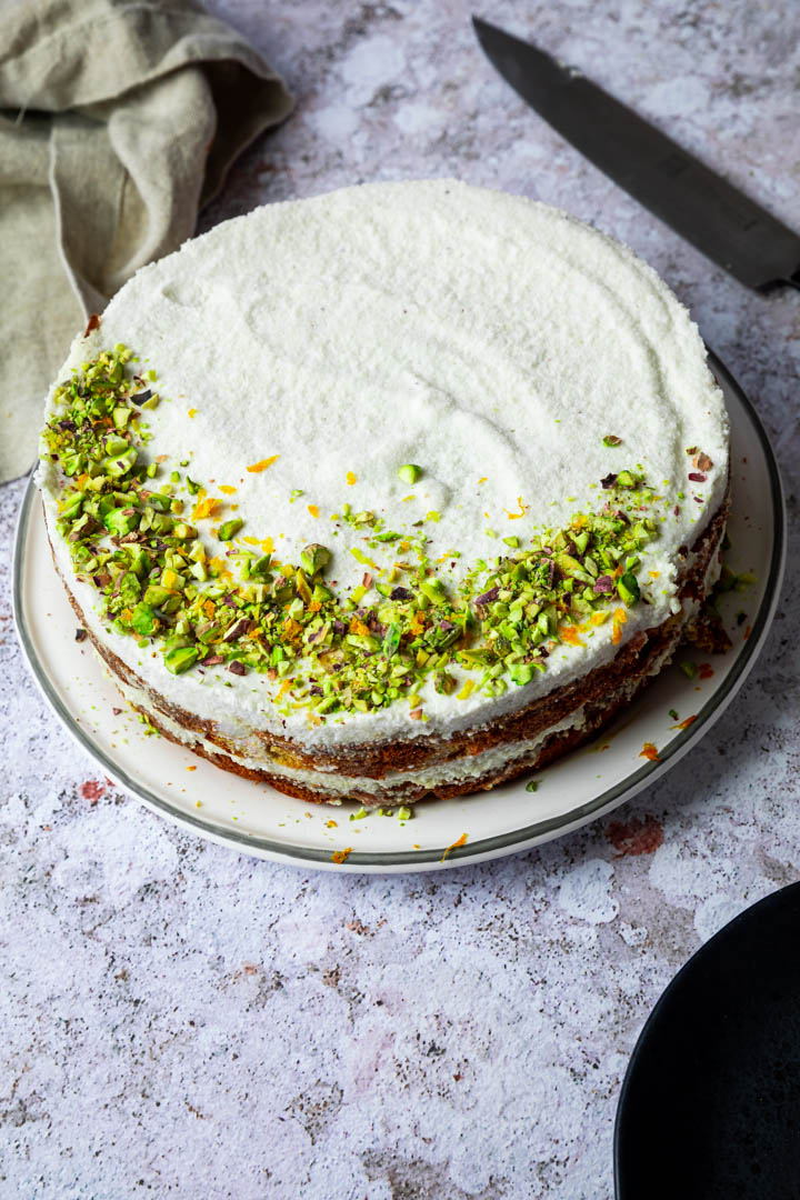 Uncut carrot cake decorated with chopped pistachios and orange zest