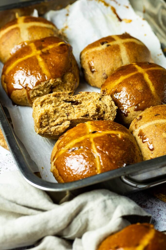 Baking Pan with Hot Cross Buns. One vegan hot cross bun is halfed to see the fluffy and pillowy inside.