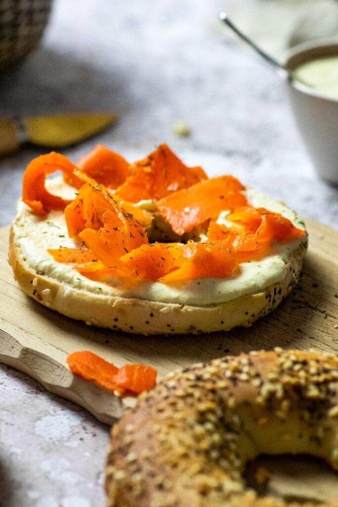 Veganer Räucherlachs aus Karotten zubereitet. Karotten Lox auf einem Bagel mit selbstgemachten ölfreien Meerrettich-Dip.
