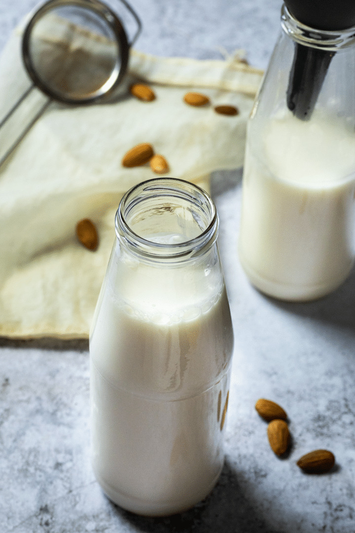 Homemade Almond Milk in a jar and in the background a sieve and a jar with almond milk