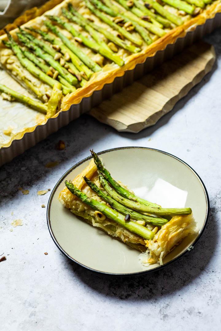 Ein Teller mit einem Stück vegane Spargel Tarte und im Hintergrund die ganze Spargel Tarte.