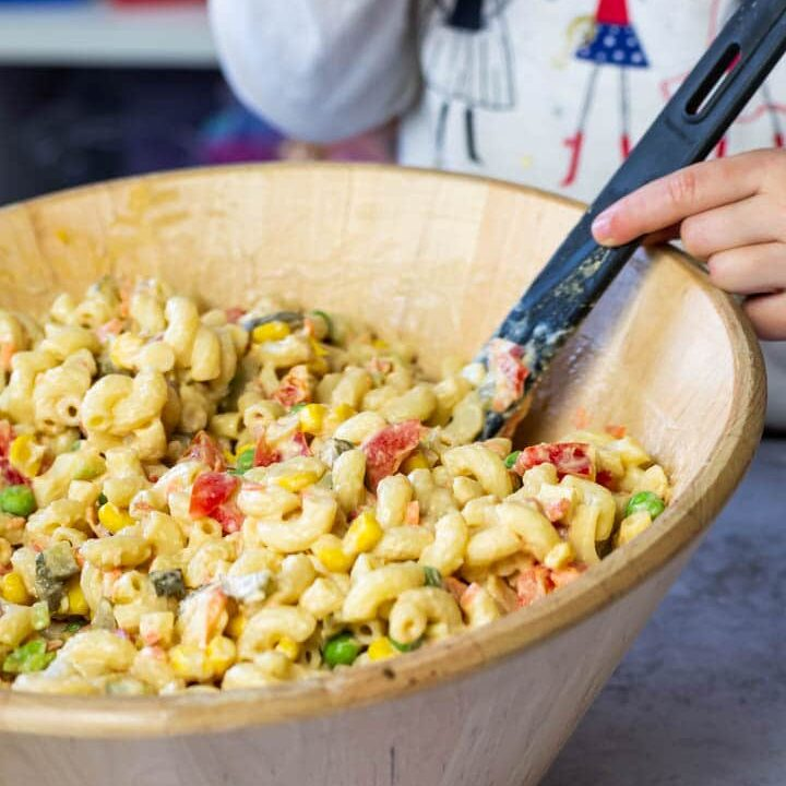 Bowl of the macaroni pasta salad. In the background my daughter holding the serving spoon.