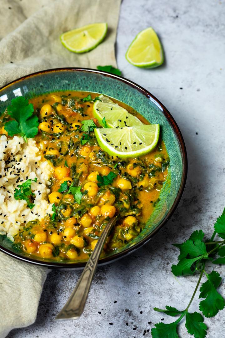 Kichererbsen Curry mit Spinat (Grünkohl) dazu Naturreis. In einer Schüssel serviert.