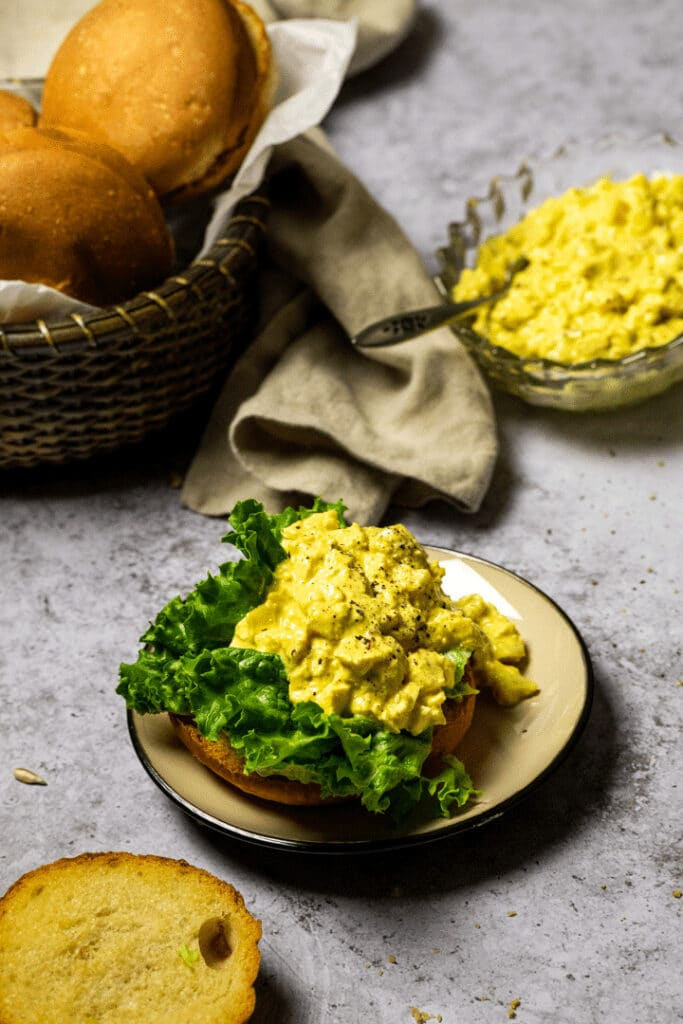 Vegan Egg Salad on a bun in the background buns in a basket and egg salad in a bowl