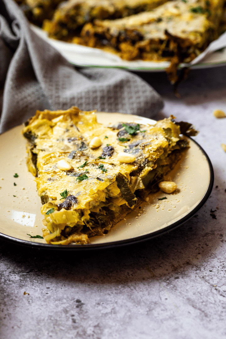 Slice of a vegan leek quiche on a plate