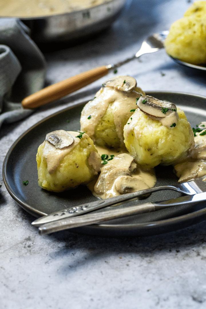 3 vegan potato dumplings on a plate with mushroom sauce