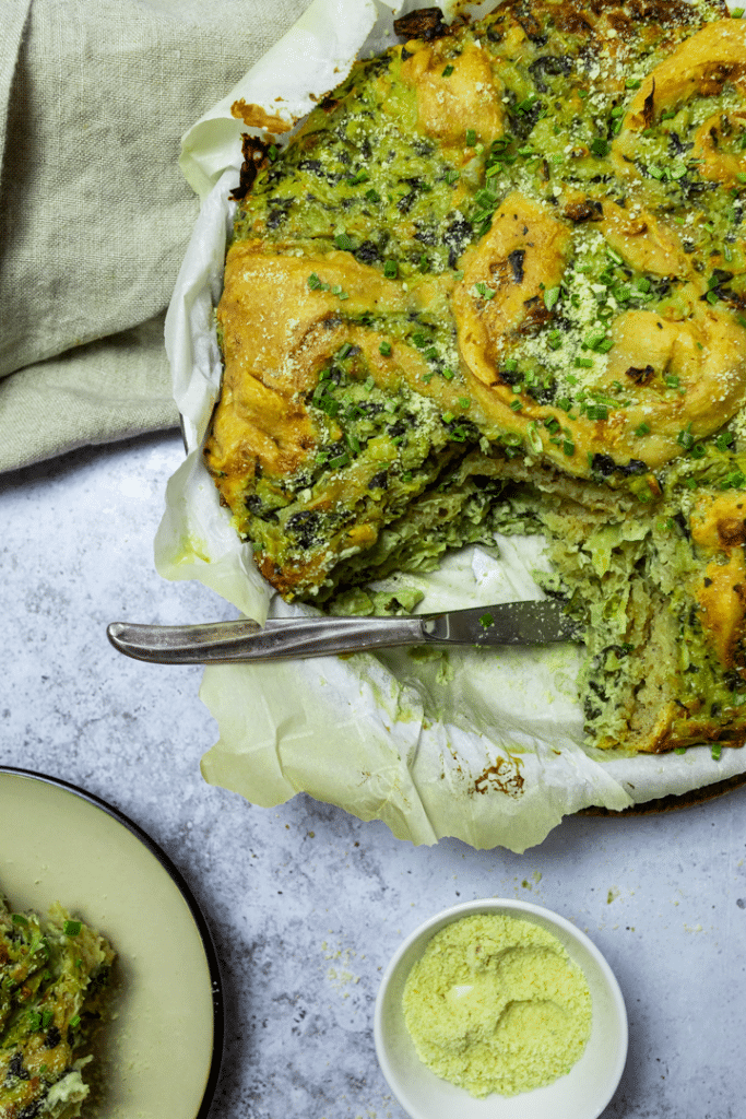 A pan with artichoke spinach pinwheels with one missing roll.