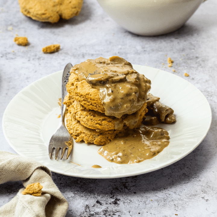 Stack of vegan biscuits on a plate with a wfpb gravy