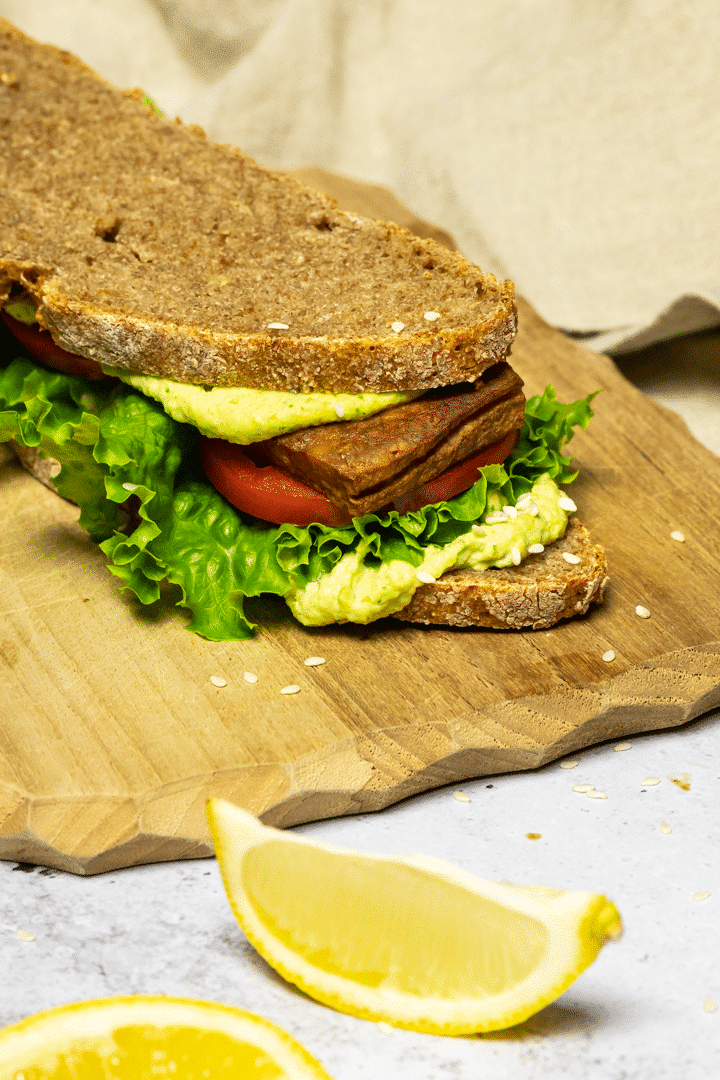 Vegan BLT Sandwich on a board made with tofu bacon, lettuce and tomatoes