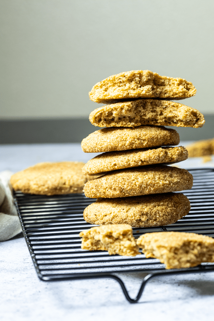 Stack of vegan wfpb snickerdoodles with some snickerdoodle pieces in front