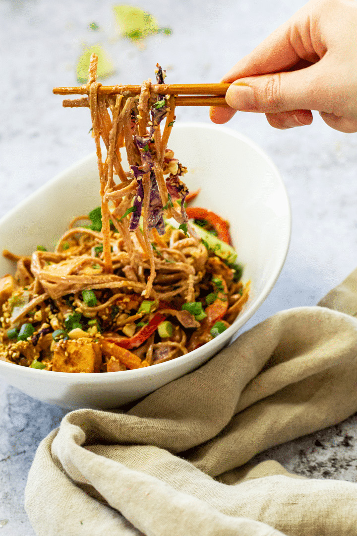 Bowl with some whole food plant-based thai peanut noodles and some are holding on asian sticks