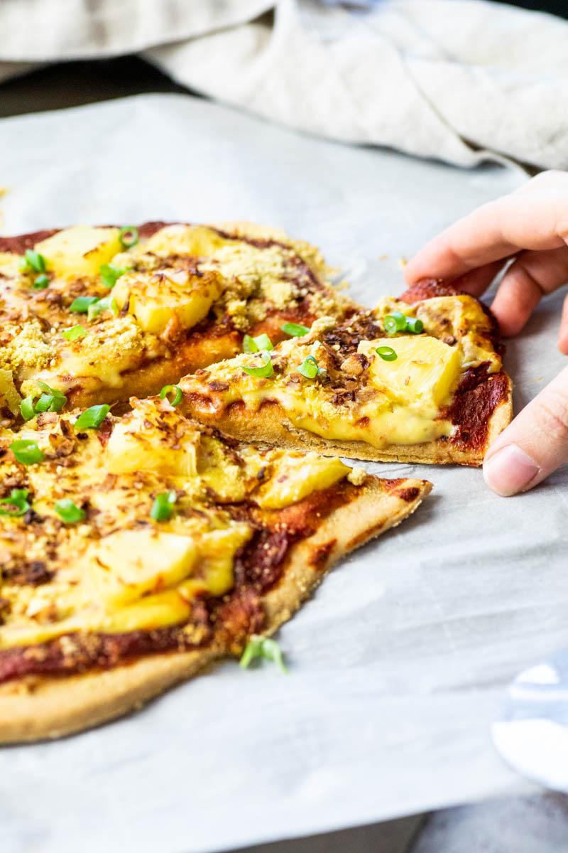 Ein veganes Pizza Hawaii-Stück schnappen
