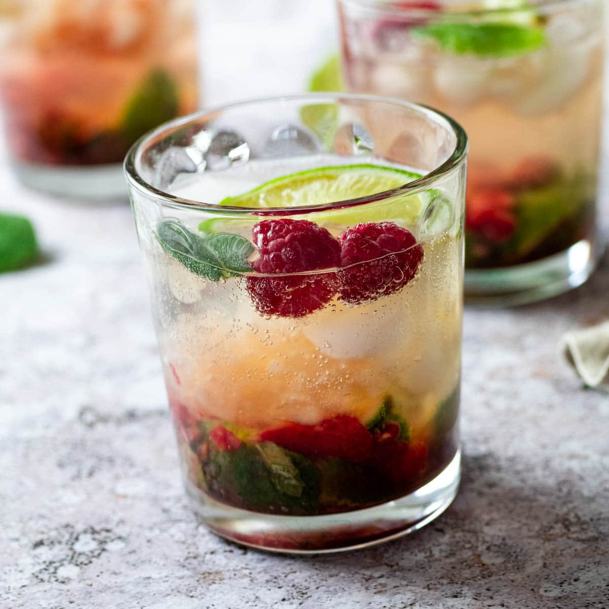 close up of a glass full with refined sugar-free raspberry mojito