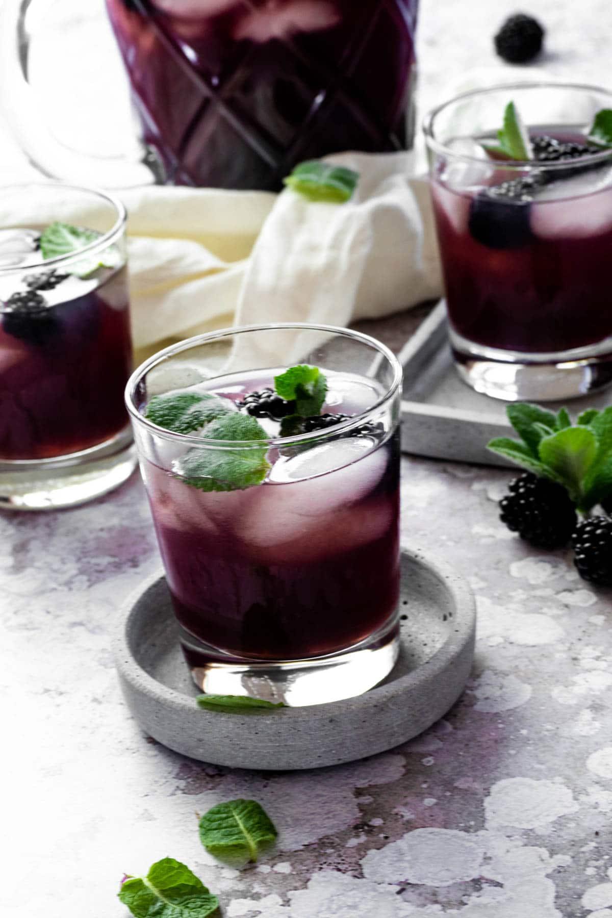 Ein Glas mit zuckerfreiem Brombeereistee auf einem Servierteller mit Gläsern und Krug im Hintergrund.