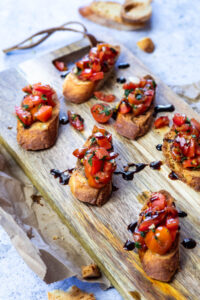 Bruschetta Crostinis served on a wooden board with one crostini in focus.