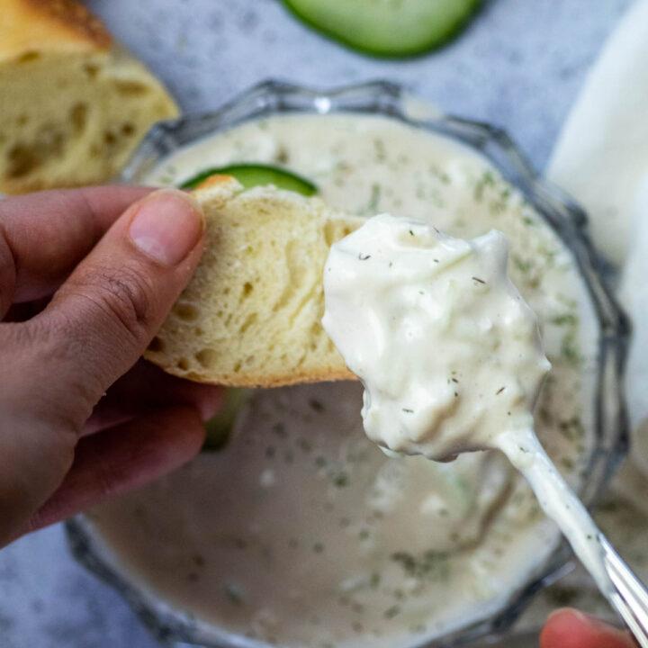 Geben etwas veganes Tzatziki auf ein Stück Baguette