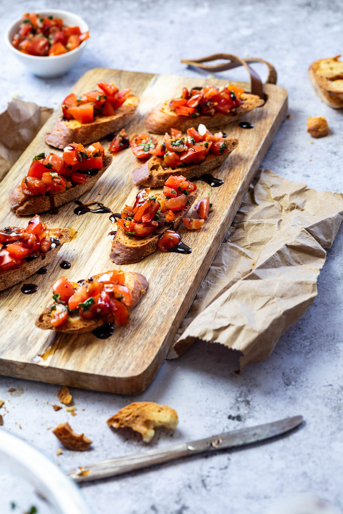 Tomato Bruschetta on Crostinis served on a cutting board with balsamic glaze drizzles.