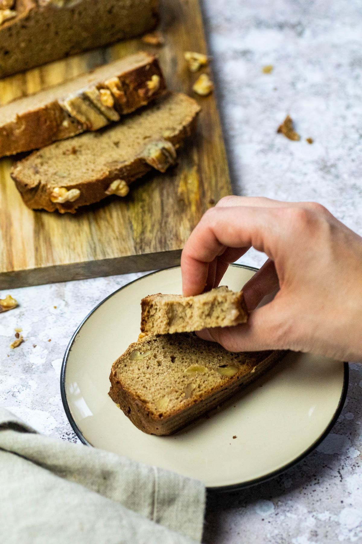 Eine Scheibe veganes Bananenbrot auf einem Teller mit einem Stück Brot.