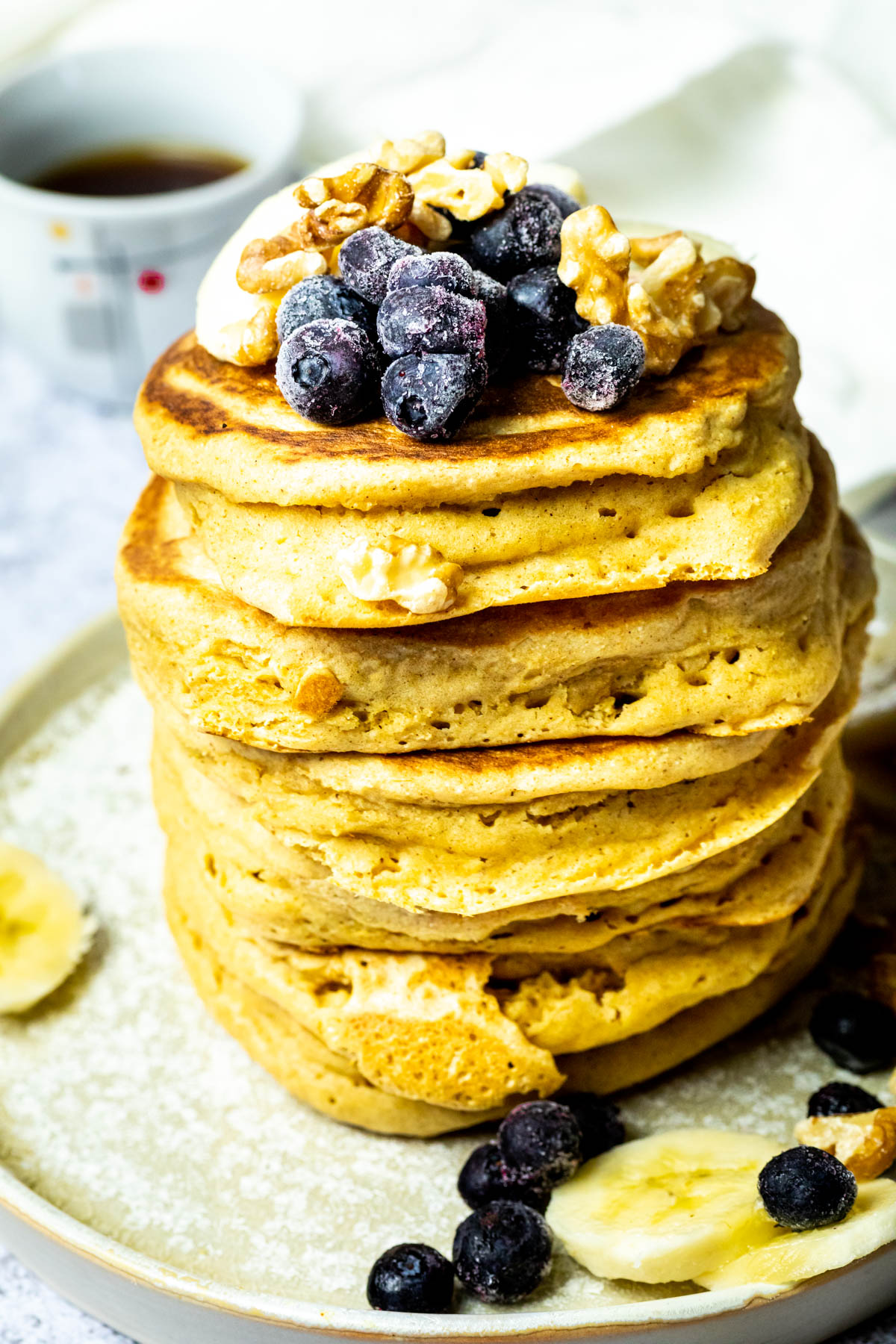 Close up of a Stack of vegan pancakes on a plate with blueberries, bananas and walnuts. And a cup of coffee in the background