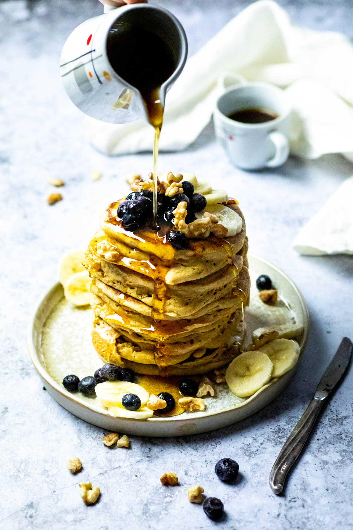 Stack of vegan pancakes on a plate with blueberries, bananas and walnuts. And a cup of coffee in the background. Pouring Maple syrup over the pancake stack.