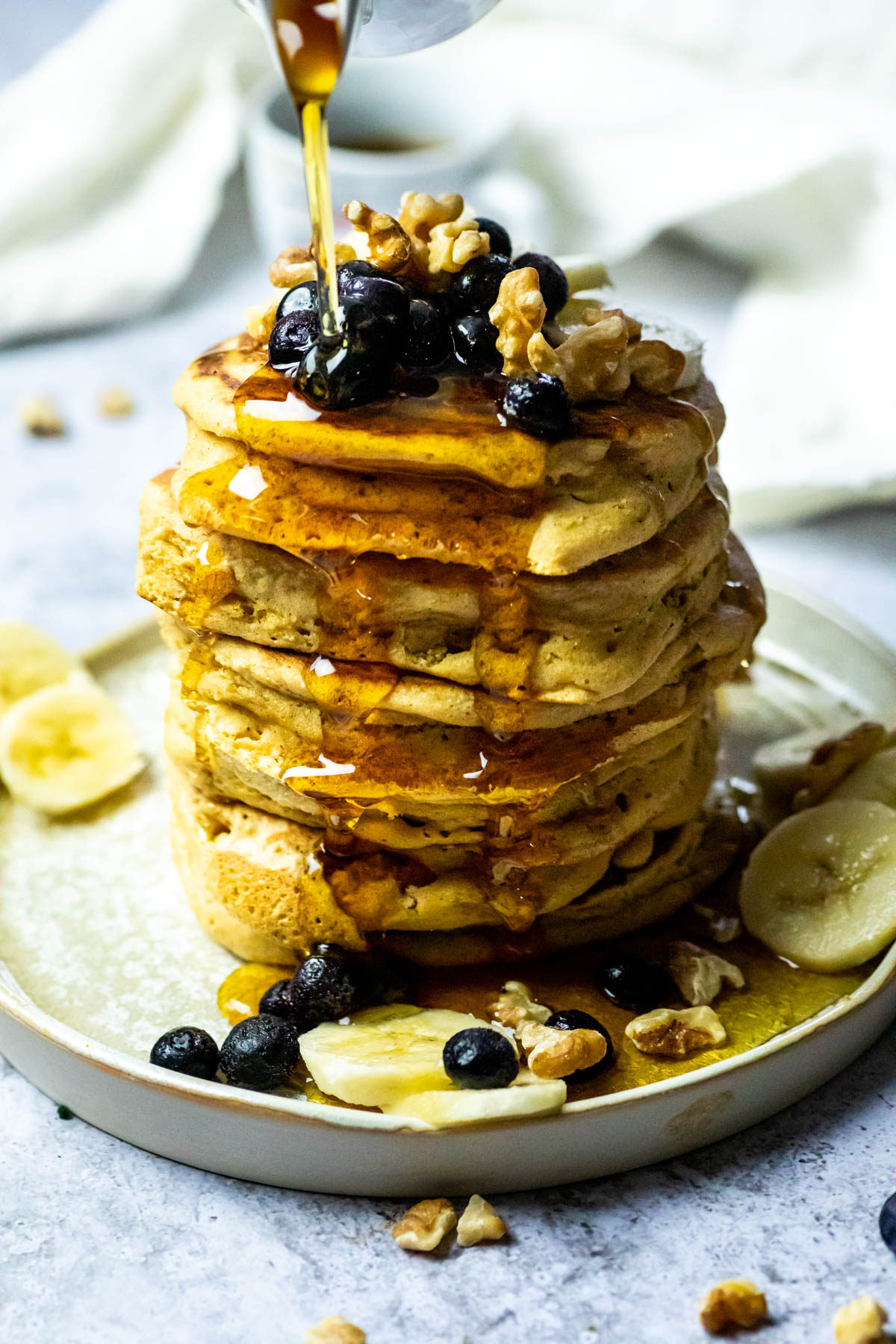 Close up of a stack of vegan pancakes and pouring some maple syrup over.