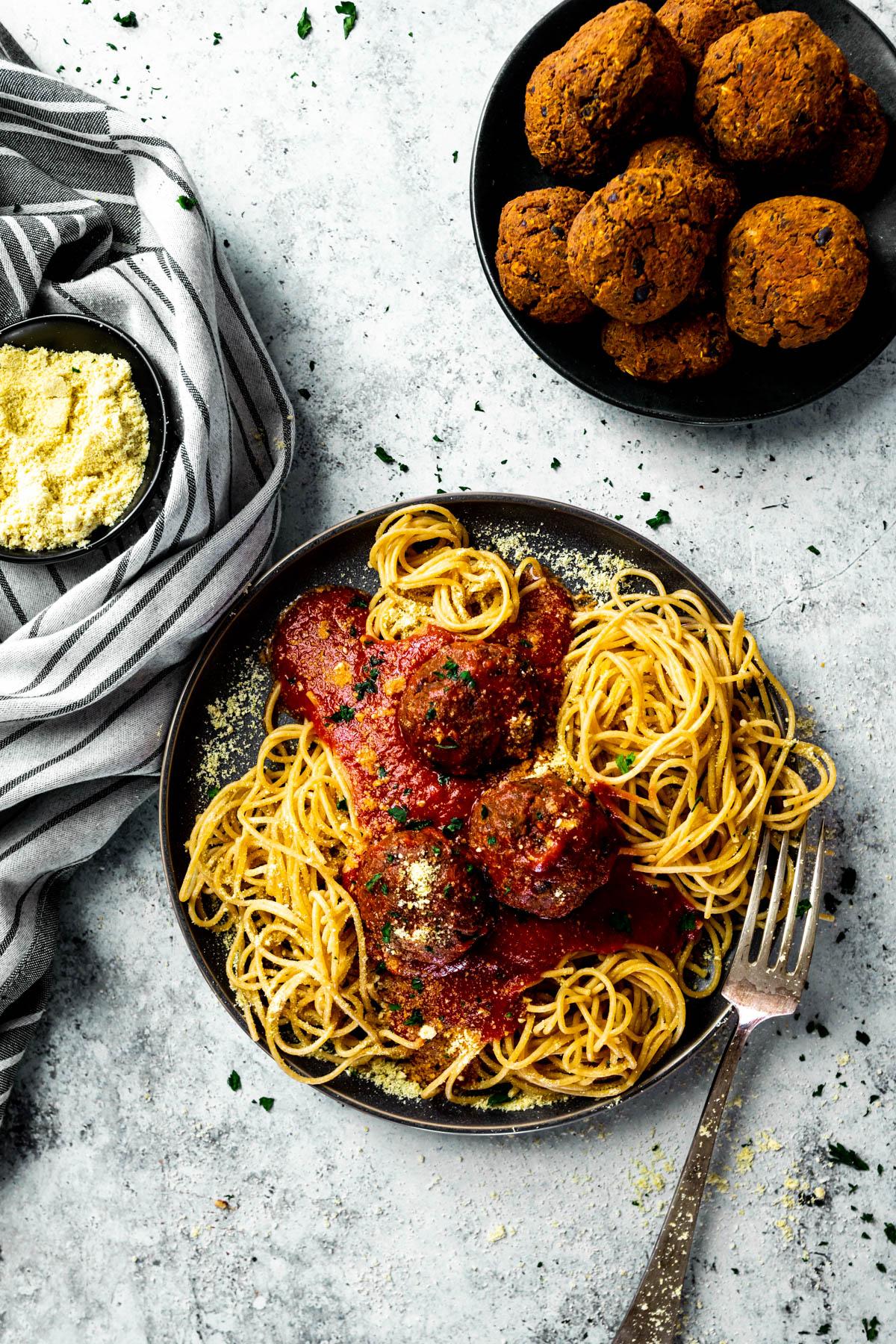 Vogelblick auf einen Teller mit Spaghetti, veganen Fleischbällchen und Marinara-Sauce und einen Teller mit Fleischbällchen und eine Schüssel mit veganem Parmesan.