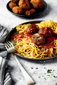 In focus vegan meatballs served on top of spaghetti and marinara sauce on a plate.