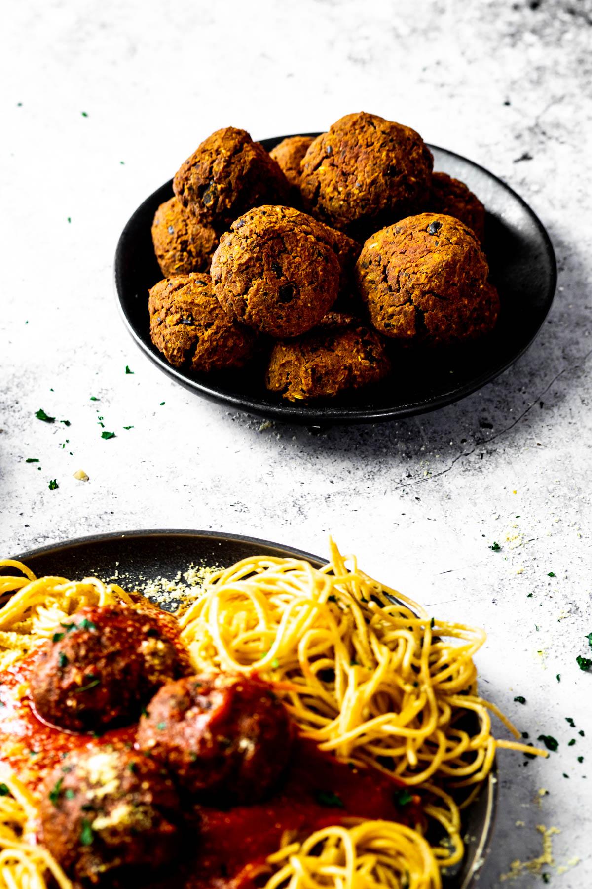 Kleiner Teller mit ein paar veganen Fleischbällchen. Und vorne verschwamm ein Teller mit Spaghetti und veganen Fleischbällchen