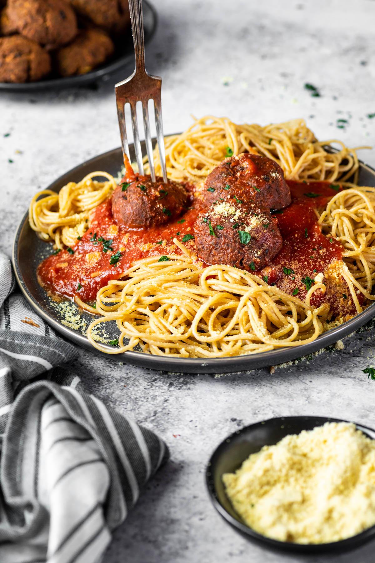Die Gabel steckt in einem veganen Fleischbällchen, das mit Spaghetti und Marinara-Sauce auf einem Teller serviert wird.
