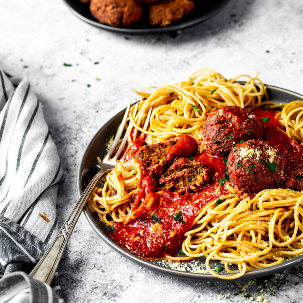 Close up of two half meatballs on spaghetti