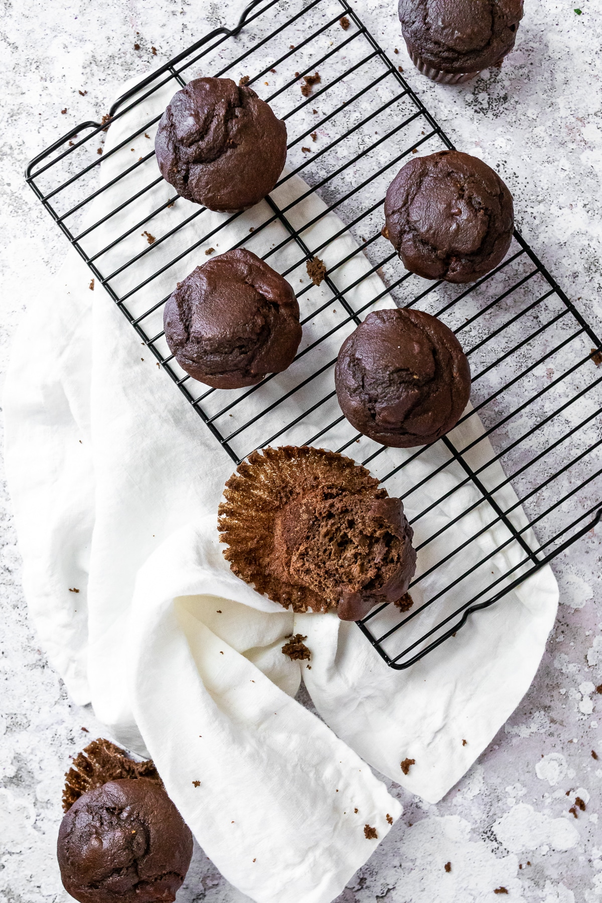 Bird view of 7 chocolate muffins on a wire rack with a cloth on the side.