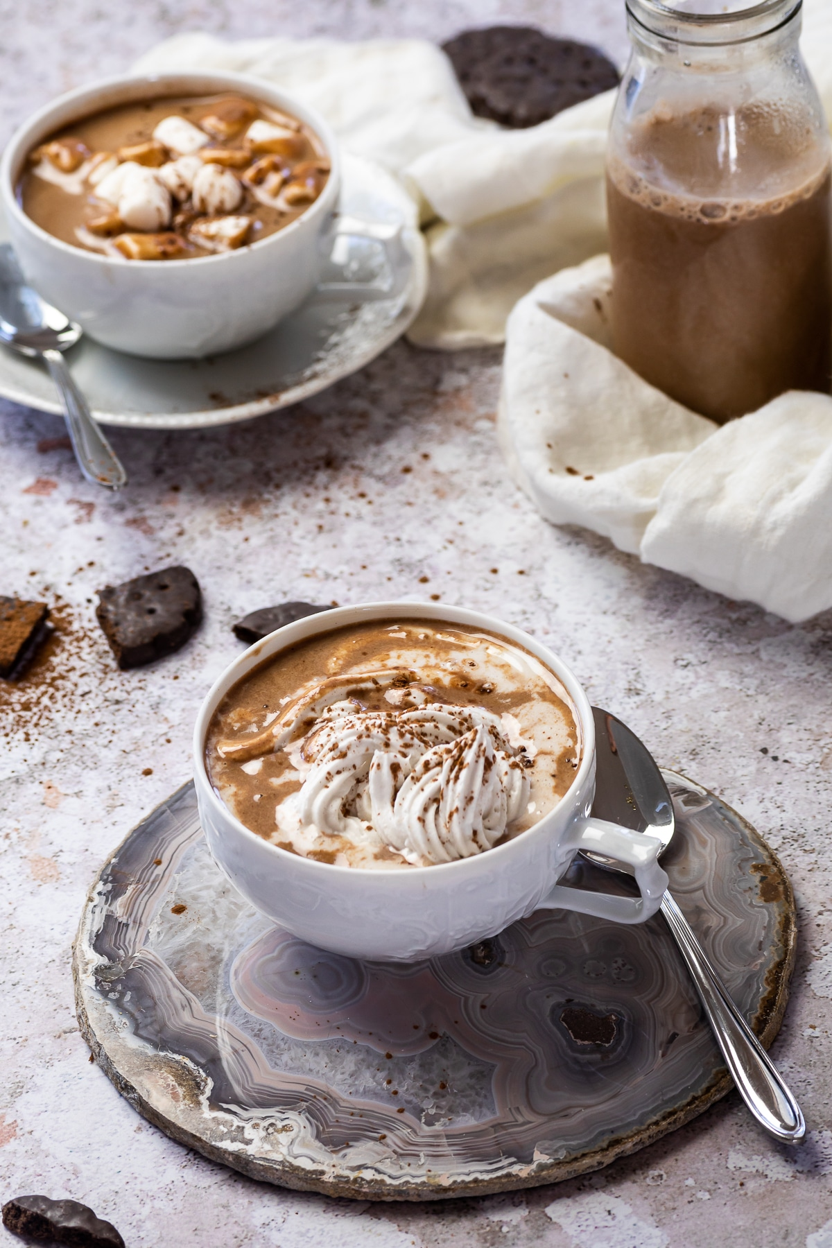 2 cups of hot chocolate one with coconut cream and one with marshmallows topped.