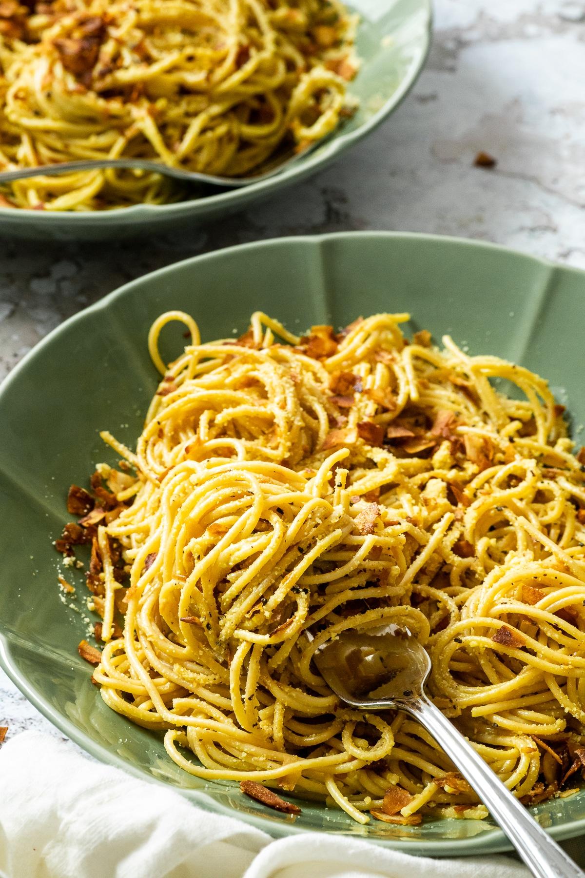 Vegane Spaghetti Carbonara serviert auf einem Teller mit einer Gabel und im Hintergrund einen verschwommenen Teller mit Pasta Carbonara.