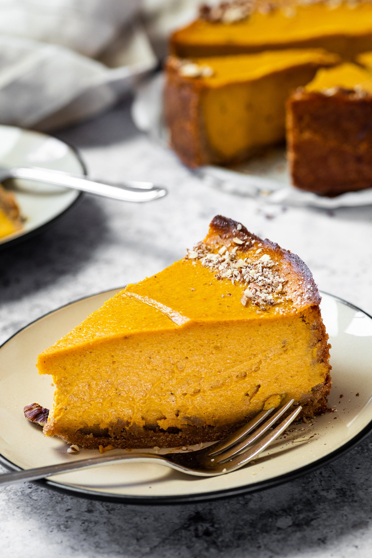 One Cheesecake with Pumpkin on a plate with the cheesecake in the background