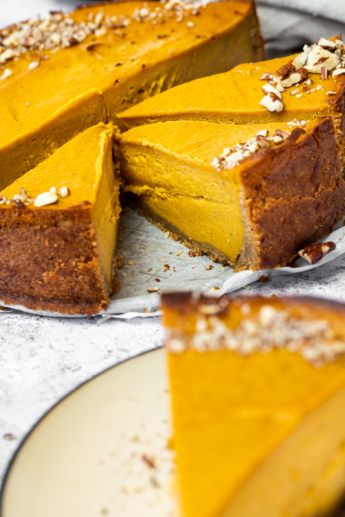 3 Cutted pumpkin Cheesecake pieces in focus with one blurred in front.