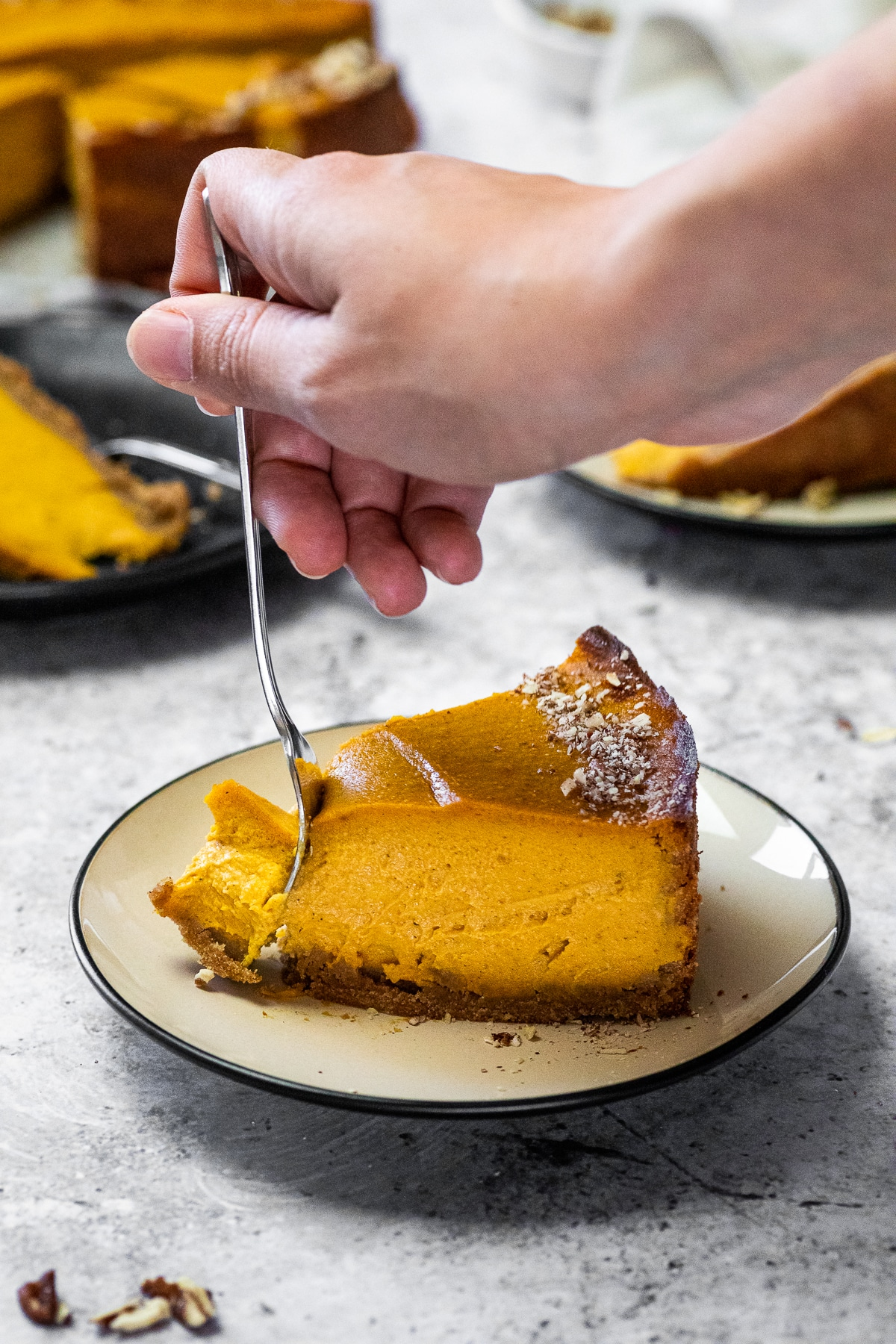 Taking some pumpkin cheesecake with a fork from a piece on a plate.