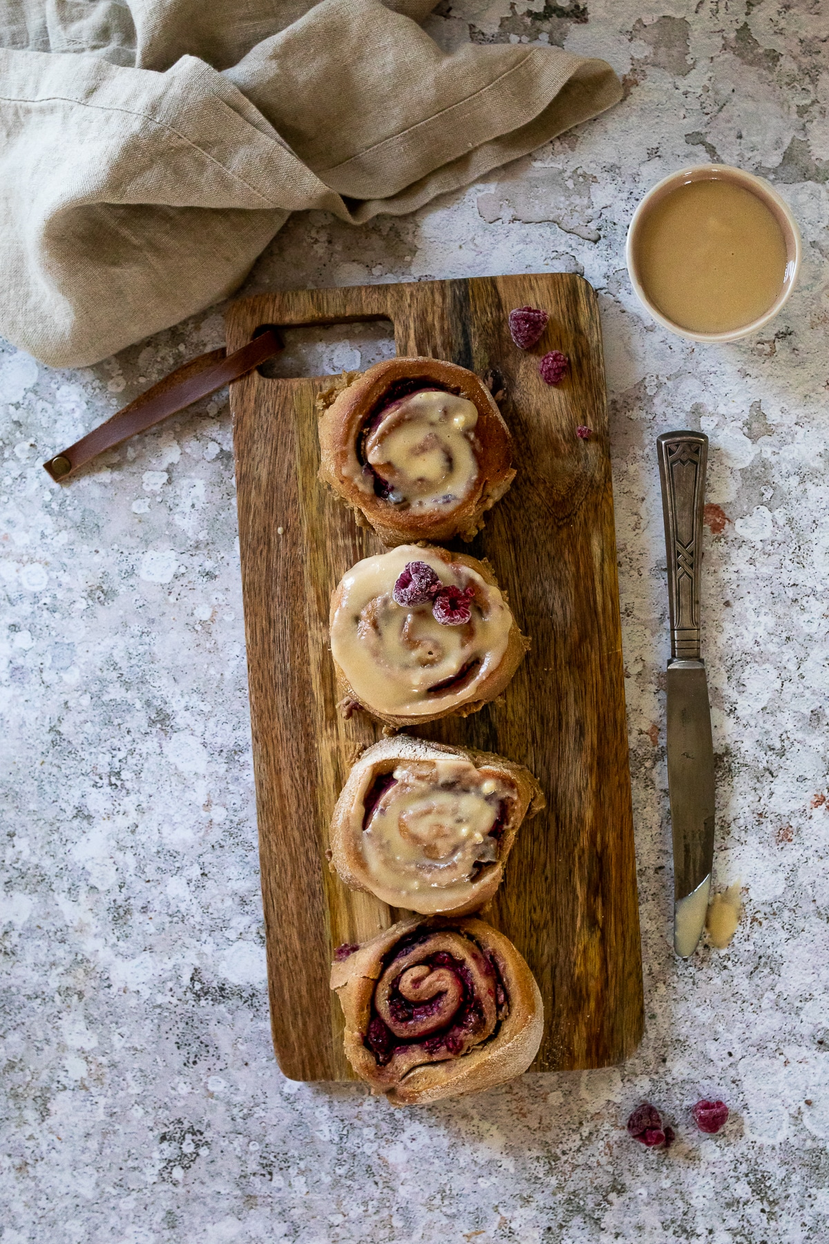 Bird View: 4 vegan raspberry cinnamon buns with an oil free frosting on a wood board with a knive on the right side and a bowl with frosting in the right upper corner.