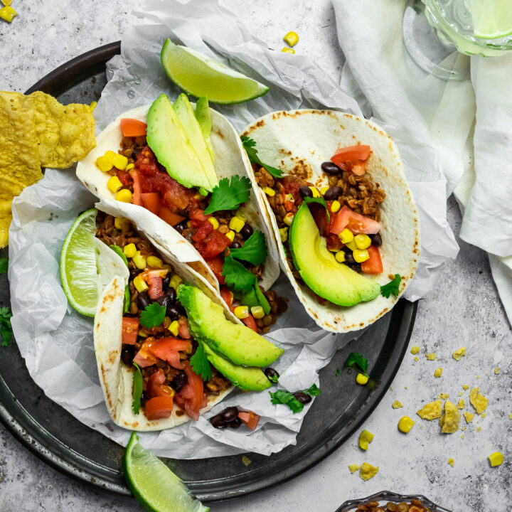 Bird view of 3 tacos on a serving plate with a bowl of vegan taco meat and a cup with water.